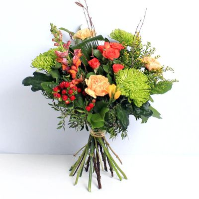 An autumn mix of green foliage, antirihnums, orange spray carnations, hypericum and green blooms