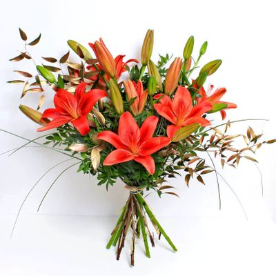 Festive Red Lilies are a great alternative to traditional Christmas flowers. The simple and elegant design is expertly arranged with tinted winter foliage by our local florists.