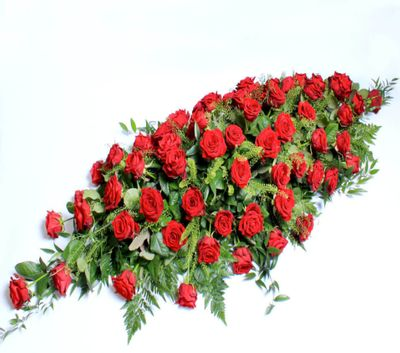 This handcrafted arrangement features hand cut red roses and perfectly expresses condolences. These ethically sourced, sustainable funeral flowers are available for same day delivery.